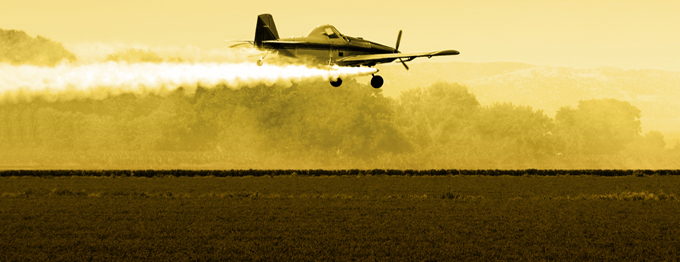 A crop duster flying over the fields in the late afternoon.
